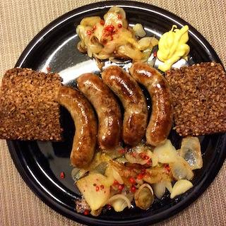 Schweinsbratwürstchen mit Zwiebelgemüse, scharfer Senf, Vollkornbrot